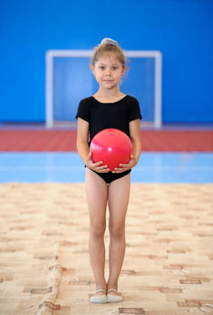 sportive: Little gymnast girl standing alone with red ball in the gym