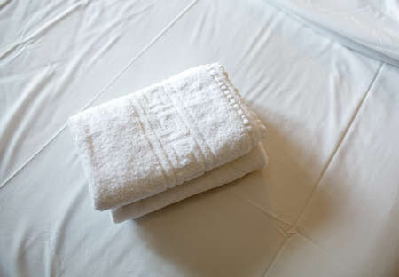 bed sheet: Close-up shot of two fresh clean towels on the bed with white sheet