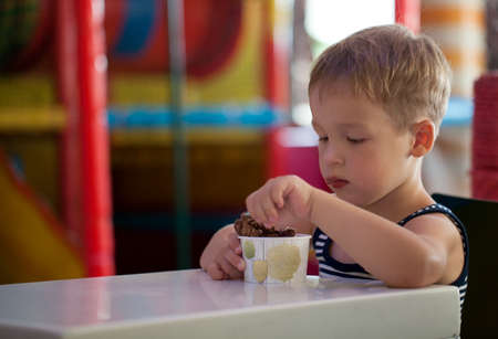 game room: Little boy having tasty chocolate ice cream sitting at the table in game room