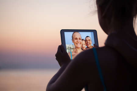 Mother, father and son making selfie using tablet computer. They taking picture on resort background photo