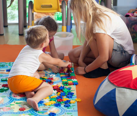 schoolmaster: Little boy and girl playing with schoolmaster in game room or nursery. Girl doing puzzle, boy playing with toy bike Stock Photo