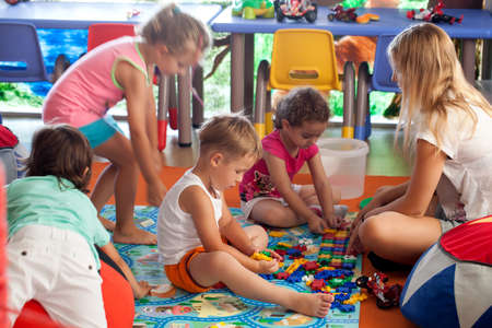 woman sitting floor: Group of children and schoolmaster in game room or nursery. Kids playing learning and active games Stock Photo
