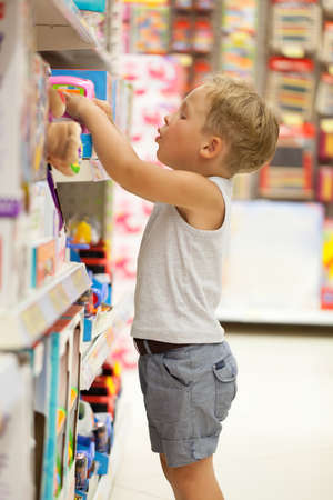 Little boy choosing toys on the high shelf in the shop