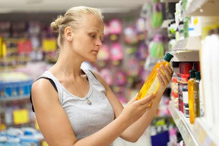 champu: Mujer joven en la tienda de elegir el champú o cosmético. Ella lectura de información en la botella