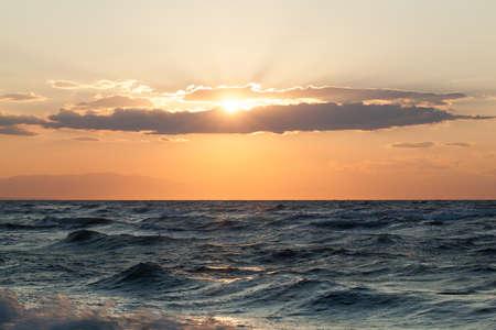 mare agitato: Vista panoramica del mare ondulato grezzo e domenica sera splende attraverso le nuvole