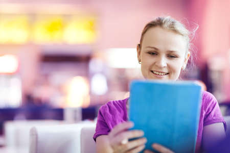 restaurant staff: Beautiful woman using tablet PC in restaurant indoors. She looks to the screen and smiling