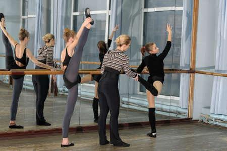 젊은 발레 댄서를 돕는 Choreographer는 올바른 위치를 가지고있다. 거울에 의해 바레에서 운동