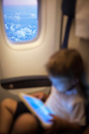 illuminator: Little boy with tablet computer in flying plane. Focus on illuminator with clouds