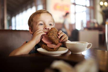 ni�os desayuno: Ni�o peque�o en una cafeter�a durante el almuerzo. Ni�o hambriento que come salchichas de su s�ndwich