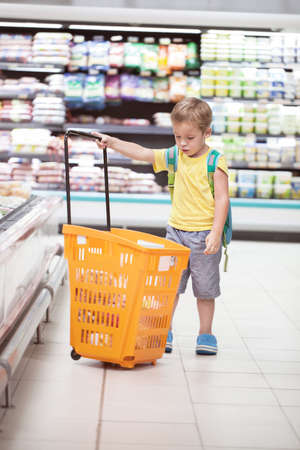 full shopping cart: Little boy in the supermarket looking at big full  shopping cart. Child going shopping alone Stock Photo