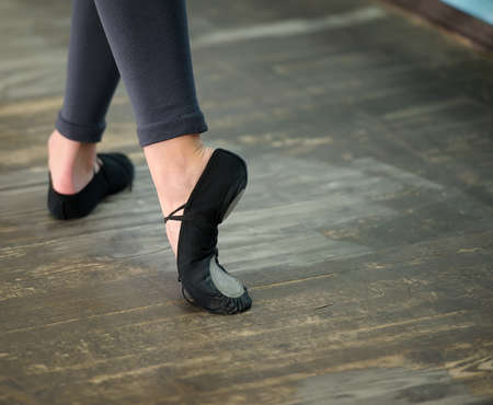 ballet slippers: Ballerinas legs in black pointes on wooden floor in point position