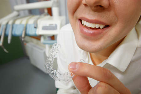 mouth smile: Close-up shot of man with big smile holding mouth guard or orthodontic retainers in dental office
