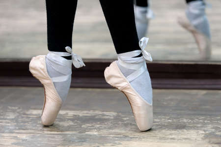 pointes: Close up view to ballerinas legs in white pointes on wooden floor in point position.