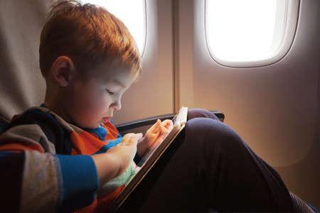 enfant banc: Petit enfant avec ordinateur tablette sur les genoux assis par l'illuminateur dans le plan Banque d'images