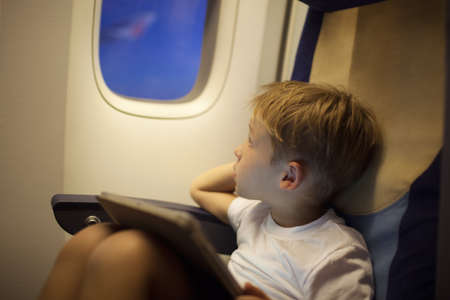 illuminator: Little boy traveling by plane. He looking out illuminator holding tablet PC on his lap