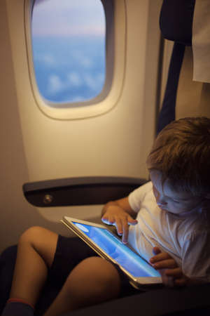 illuminator: Little boy in the plane sitting by the illuminator and using touch pad to entertain himself