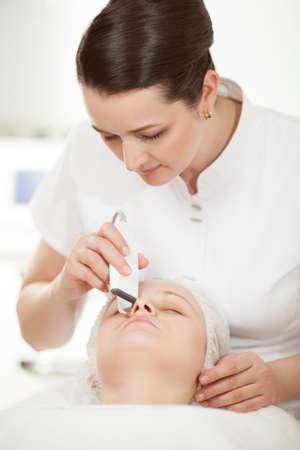 pulizia viso: Estetista professionale fornendo pulizia del viso ad ultrasuoni al salone di trattamento di bellezza Archivio Fotografico