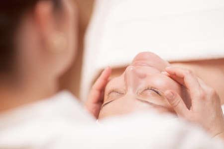 Close-up shot van jonge vrouw krijgt professionele gezicht massage op schoonheidsbehandeling salon. Focus op een vrouw Stockfoto