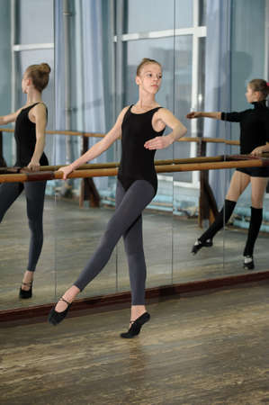 practices: Girls exercising at the barre during ballet class and reflecting in the mirror Stock Photo