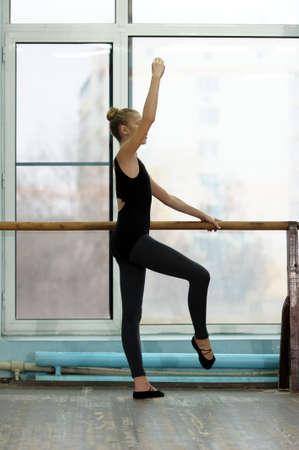 ballet: Joven bailarina de ballet femenino ejercicio en la barra de la ventana en estudio. Clases de ballet