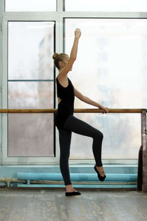 barre: Young female ballet dancer exercising at the barre by the window in studio. Ballet classes