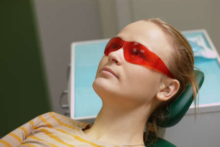 arm chair: Young woman in red safety glasses lying in arm chair in dental office