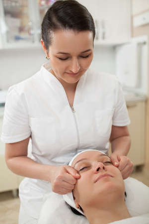 cosmetician: Professional cosmetician at work. She giving a woman face massage at beauty spa