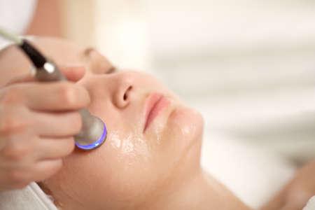 masaje facial: Close-up shot de la mujer recibiendo tratamiento facial profesional con un equipo especial. Cosmetician procedimiento de elevaci�n hacer Foto de archivo