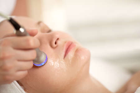 Close-up shot of woman getting professional facial treatment with special equipment. Cosmetician doing lifting procedure