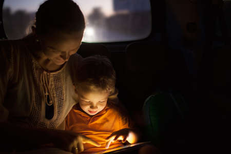 child seat: Mother and little son traveling by car at night. They using tablet computer to entertain themselves during trip. Pad screen shining brightly in dark car Stock Photo