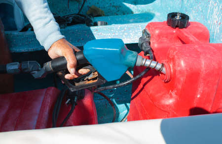 boat motor: Close-up shot of a man fueling red plastic tank of a motor boat with petrol Stock Photo