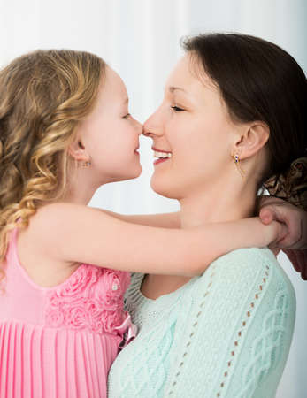 touching noses: Beautiful mother and daughter touching each other with their noses. Lovely family portrait Stock Photo