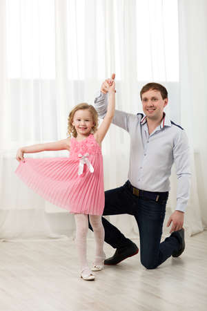 dad and daughter: Father and little daughter dancing. Little princess in pink dress walking around dad standing on knee
