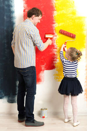 brighter: Father and little daughter having fun while painting wall in different colors. Make your life brighter