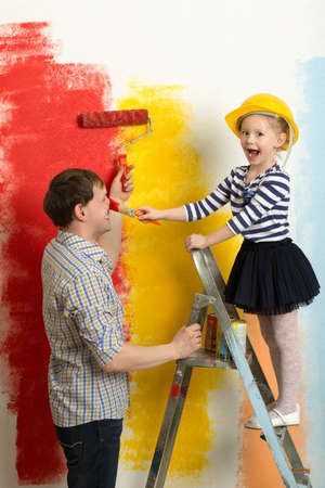 Girl and father fooling while painting wall in bright colors. Girl in hard hat standing on stepladder painting dadys nose photo