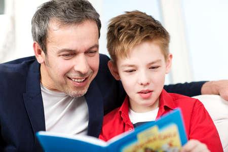 ni�os estudiando: Padre e hijo felices de pasar tiempo en la lectura. Pap� mira en el libro muchachos