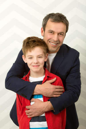 proud: Family portrait of happy proud father hugging smiling son. Parents love Stock Photo
