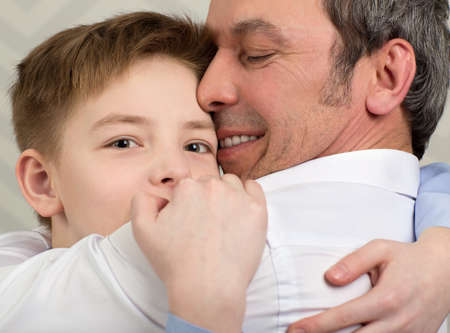 Close-up shot of a son giving father a hug. Boy devoted to his beloved dad
