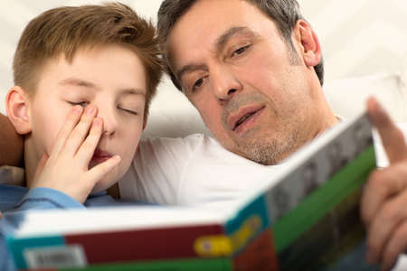 bedtime: Close-up shot of a father reading a book to the son who is already sleepy and rubbing his eyes Stock Photo