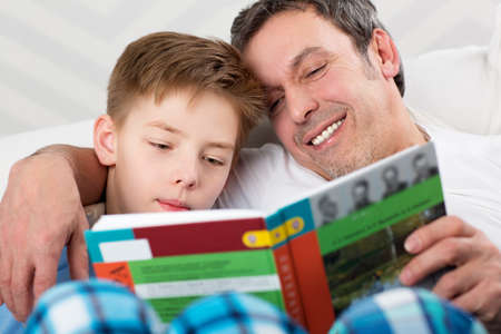 Father and son reading a book. Careful dad helping child to learn new things