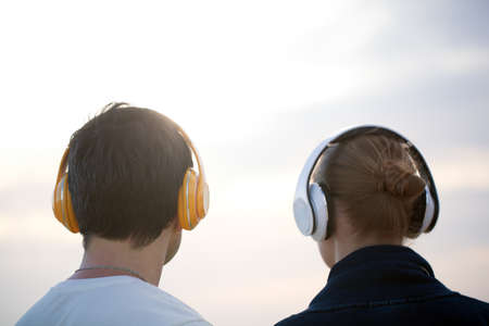 listening back: Back shot of man and woman listening to music in wireless headphones against evening cloudy sky background