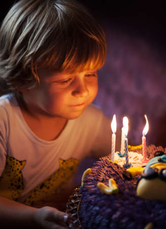 child birthday: Little boy blows out candles in the cake for his 4th birthday Stock Photo