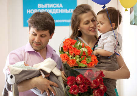 happy life: Family in the maternity hospital, father holds infant, mother with flowers holds elder son