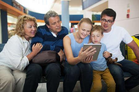 abuelos: Gran familia feliz en el aeropuerto. Niños, padres y abuelos miran algo en la computadora de la tableta para llenar en el tiempo mientras espera en el salón