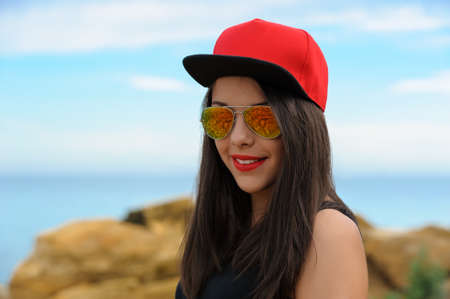 brunette girl: Young beautiful smiling brunette girl in red cap and sun glasses against blue sky Stock Photo