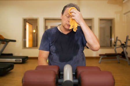 wiping: Exhausted mature man wiping sweat with a towel after intensive training in the gym Stock Photo