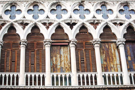 stained glass windows: Ancient building in Venice, Italy. Worn and grungy facade with columns and stained glass windows