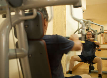 perspire: Mature man working out on shoulder press machine. Regular physical activity for keeping fit and healthy. Shot in motion and mirror reflection Stock Photo