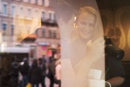 show window: Man and woman are sitting in cafe, he shows photos in the camera to her. The shot is made through the cafe show window. Stock Photo