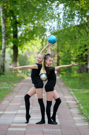 sports training: Two graceful gymnast girls posing with balls which are held with their hands and backs. Outdoor shot on bright summer day